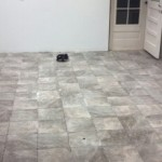 cleaning excess grout from new tile kitchen floor.
