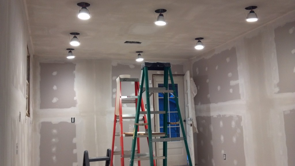 Hanging new recessed LED lighting in kitchen remodel.